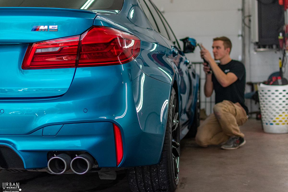 Detailer performs paint correction exterior service on BMW M3