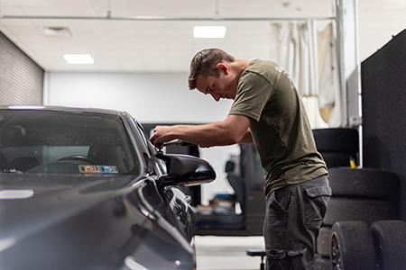 Detail Technician Performing Paint Correction Inspection Detailing Service